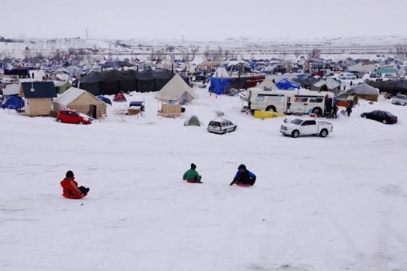"Children sled down a hill inside of the Oceti Sakowin camp as ""water protectors"" continue to demonstrate against plans to pass the Dakota Access pipeline near the Standing Rock Indian Reservation, near Cannon Ball, North Dakota, U.S., December 2, 2016. REUTERS/Lucas Jackson"