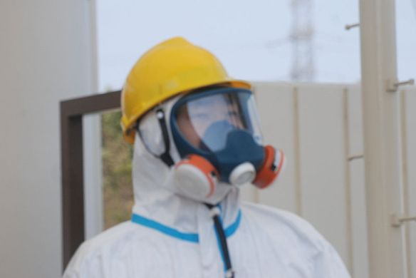 One of the gate guards in a hazmat suit, helmet and dual intake respirator